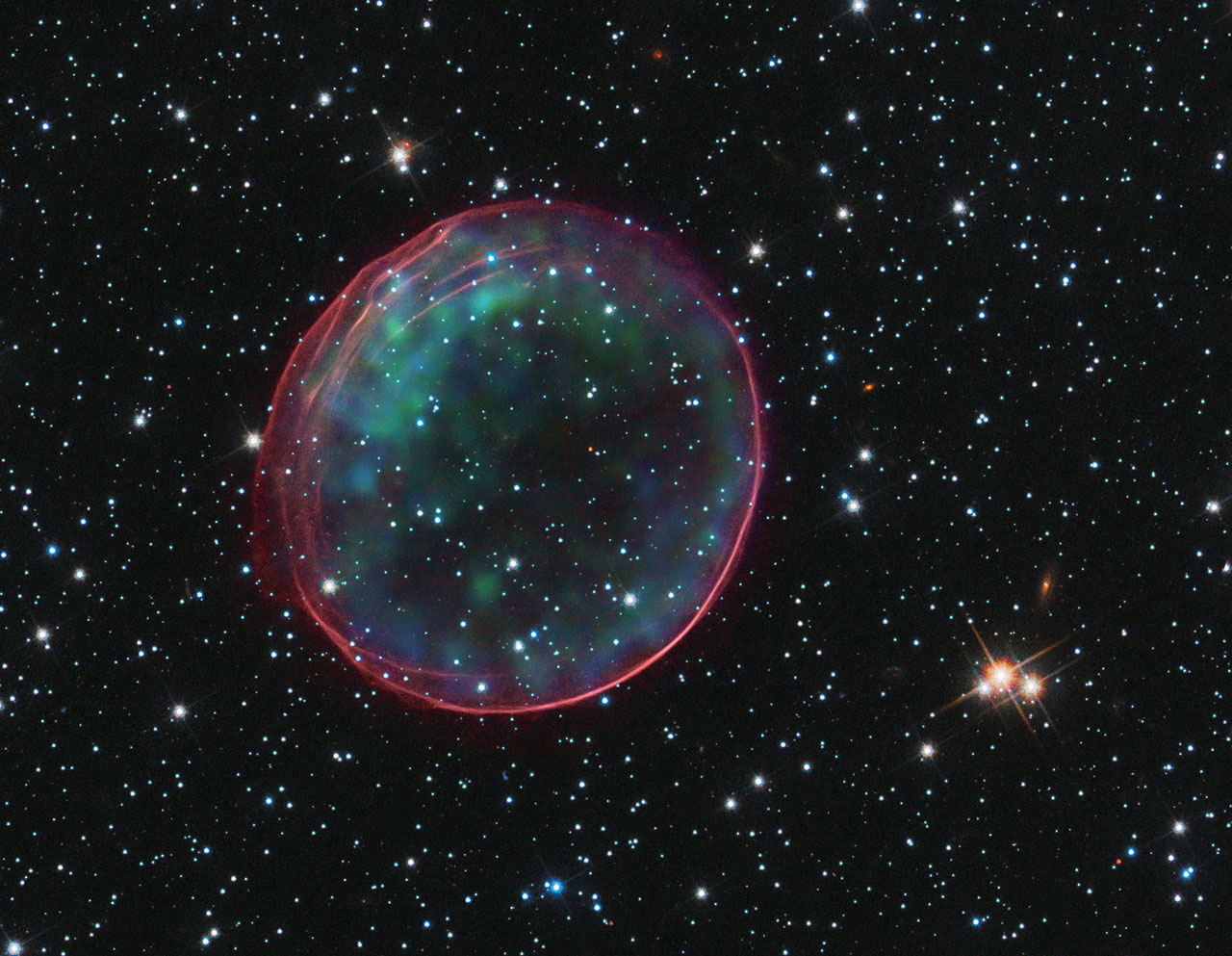 This delicate shell, photographed by the NASA/ESA Hubble Space Telescope, appears to float serenely in the depths of space, but this apparent calm hides an inner turmoil. The gaseous envelope formed as the expanding blast wave and ejected material from a supernova tore through the nearby interstellar medium. Called SNR B0509-67.5 (or SNR 0509 for short), the bubble is the visible remnant of a powerful stellar explosion in the Large Magellanic Cloud (LMC), a small galaxy about 160 000 light-years from Earth. Ripples in the shell's surface may be caused either by subtle variations in the density of the ambient interstellar gas, or possibly be driven from the interior by fragments from the initial explosion. The bubble-shaped shroud of gas is 23 light-years across and is expanding at more than 18 million km/h. Hubble's Advanced Camera for Surveys observed the supernova remnant on 28 October 2006 with a filter that isolates light from the glowing hydrogen seen in the expanding shell. These observations were then combined with visible-light images of the surrounding star field that were imaged with Hubble's Wide Field Camera 3 on 4 November 2010, and archival X-ray observations taken by NASA's Chandra X-ray Observatory.