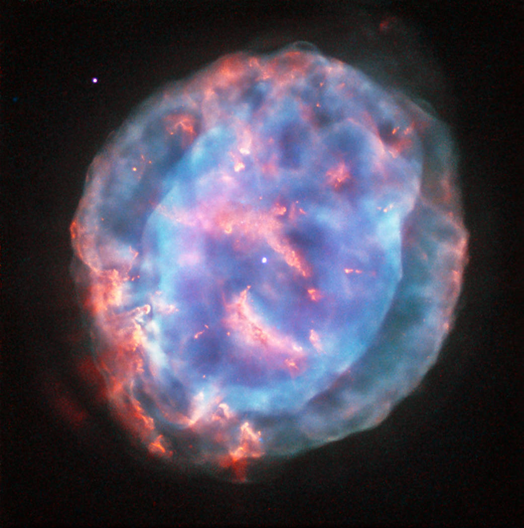 This colourful bubble is a planetary nebula called NGC 6818, also known as the Little Gem Nebula. It is located in the constellation of Sagittarius (The Archer), roughly 6000 light-years away from us. The rich glow of the cloud is just over half a light-year across — humongous compared to its tiny central star — but still a little gem on a cosmic scale. When stars like the Sun enter retirement, they shed their outer layers into space to create glowing clouds of gas called planetary nebulae. This ejection of mass is uneven, and planetary nebulae can have very complex shapes. NGC 6818 shows knotty filament-like structures and distinct layers of material, with a bright and enclosed central bubble surrounded by a larger, more diffuse cloud. Scientists believe that the stellar wind from the central star propels the outflowing material, sculpting the elongated shape of NGC 6818. As this fast wind smashes through the slower-moving cloud it creates particularly bright blowouts at the bubble's outer layers. Hubble previously imaged this nebula back in 1997 with its Wide Field Planetary Camera 2, using a mix of filters that highlighted emission from ionised oxygen and hydrogen (opo9811h). This image, while from the same camera, uses different filters to reveal a different view of the nebula. A version of the image was submitted to the Hubble's Hidden Treasures image processing competition by contestant Judy Schmidt.