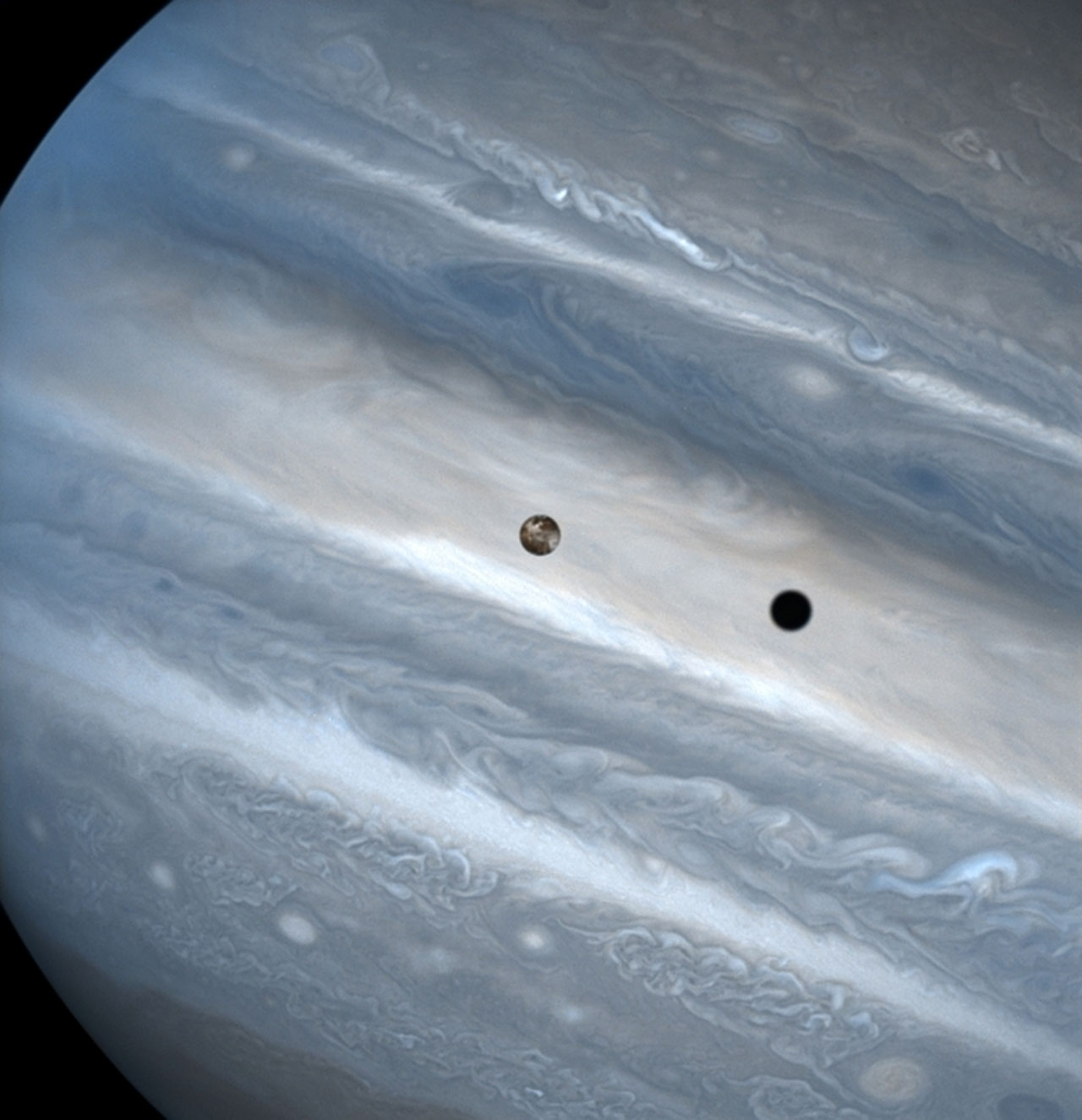 The three snapshots of the volcanic moon rounding Jupiter were taken over a 1.8-hour time span. Io is roughly the size of Earth's moon but 2,000 times farther away. In two of the images, Io appears to be skimming Jupiter's cloud tops, but it's actually 310, 000 miles (500,000 kilometers) away. Io zips around Jupiter in 1.8 days, whereas the moon circles Earth every 28 days. The conspicuous black spot on Jupiter is Io's shadow and is about the size of the moon itself (2,262 miles or 3,640 kilometers across). This shadow sails across the face of Jupiter at 38,000 mph (17 kilometers per second). The smallest details visible on Io and Jupiter measure 93 miles (150 kilometers) across, or about the size of Connecticut.
