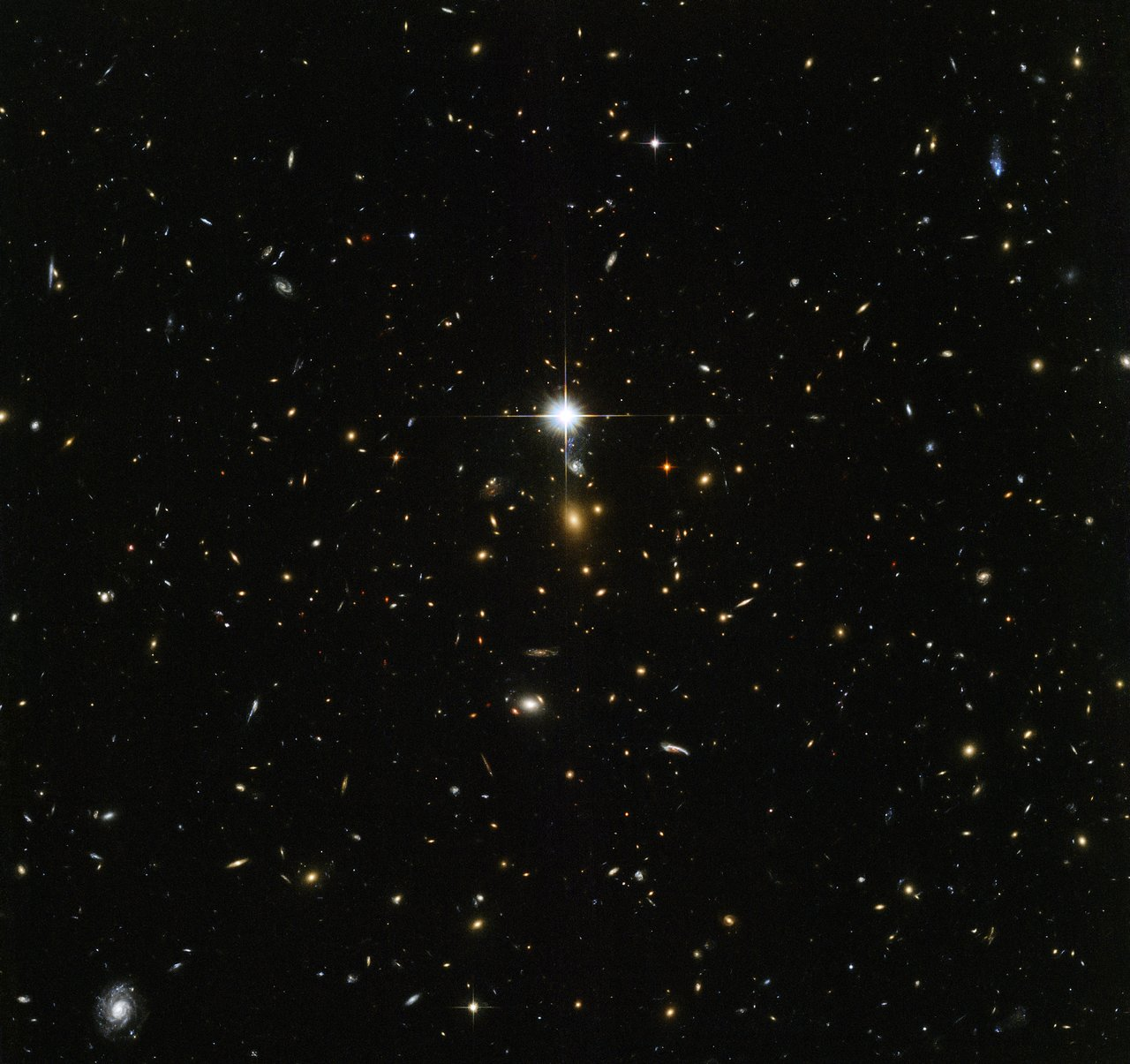 This NASA/ESA Hubble Space Telescope image is chock-full of galaxies — each glowing speck is a different galaxy, bar the bright flash in the middle of the image which is actually a star lying within our own galaxy that just happened to be in the way. At the centre of the image lies something especially interesting, the centre of the massive galaxy cluster called WHL J24.3324-8.477, including the brightest galaxy of the cluster. The Universe contains structures on various scales — planets collect around stars, stars collect into galaxies, galaxies collect into groups, and galaxy groups collect into clusters. Galaxy clusters contain hundreds to thousands of galaxies bound together by gravity. Dark matter and dark energy play key roles in the formation and evolution of these clusters, so studying massive galaxy clusters can help scientists to unravel the mysteries of these elusive phenomena. This infrared image was taken by Hubble's Advanced Camera for Surveys and Wide-Field Camera 3 as part of an observing programme called RELICS (Reionization Lensing Cluster Survey). RELICS imaged 41 massive galaxy clusters with the aim of finding the brightest distant galaxies for the forthcoming NASA/ESA/CSA James Webb Space Telescope (JWST) to study. Such research will tell us more about our cosmic origins.
