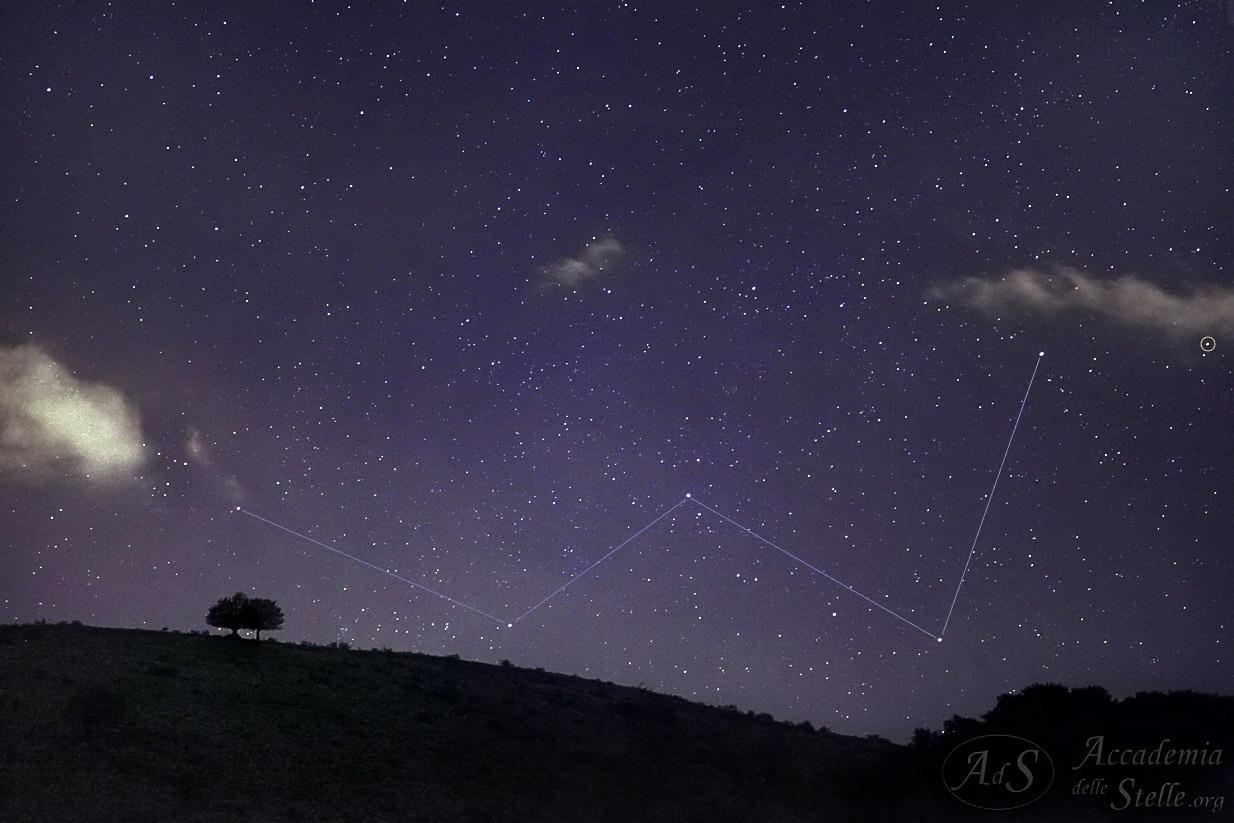 """La notissima """"W"""" di Cassiopea sorge sopra una montagna sormontata da due alberi, insieme alla stella usualmente ritenuta la più lontana visibile ad occhio nudo, evidenziata dal cerchietto sul lato destro della foto."""