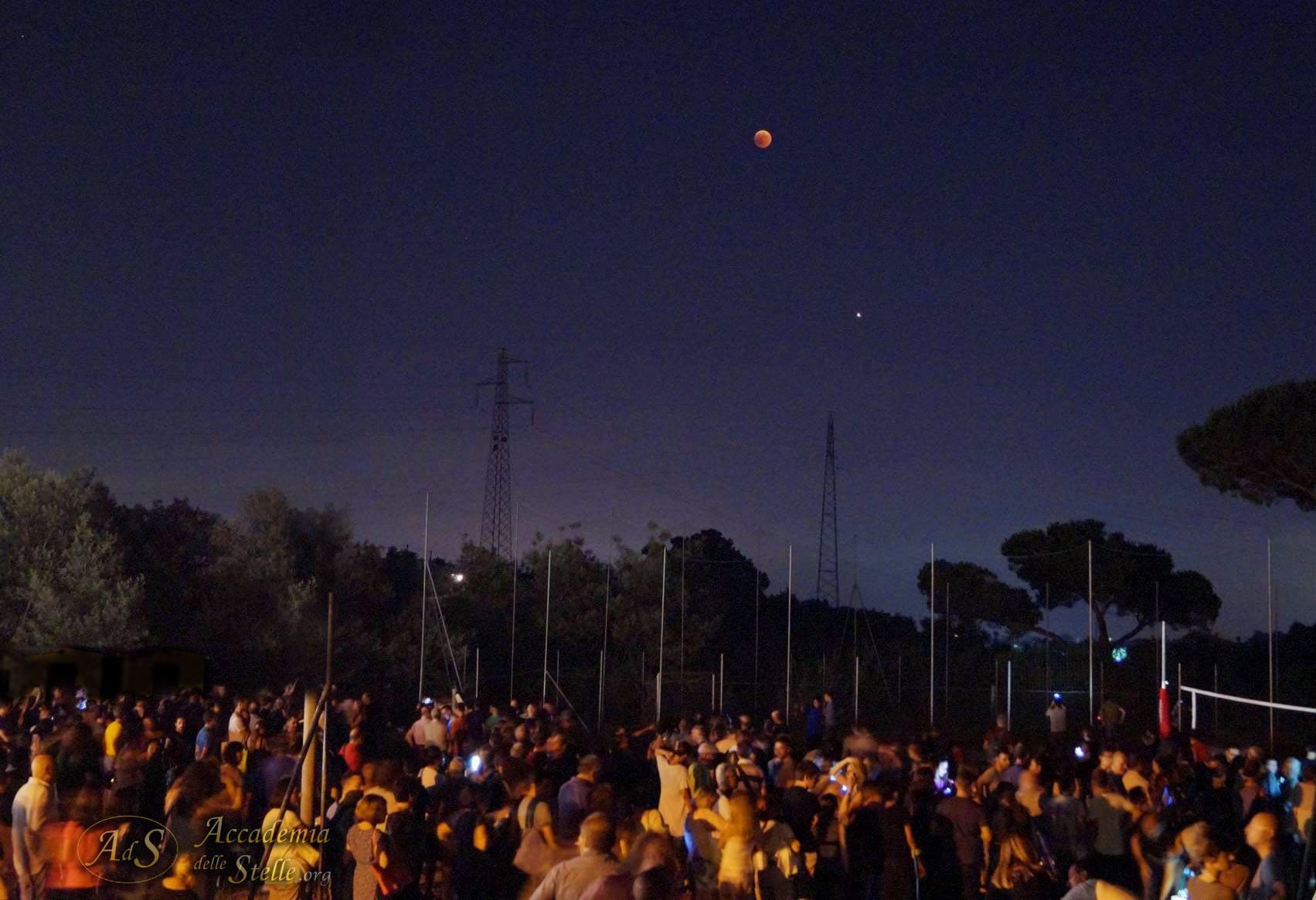 La folla radunata attorno ai telescopi di Accademia Delle Stelle - Astronomia fotografata sotto l'eccezionale coppia della serata astronomica: Luna in eclissi totale e Marte alla Grande Opposizione!